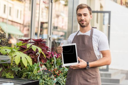 handsome florist holding tablet with blank screen near flower shop and looking at camera