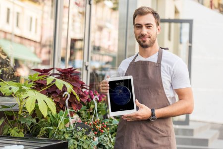 handsome florist holding ipad near flower shop and looking at camera