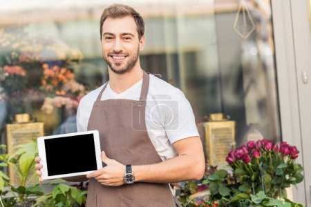 smiling handsome florist holding tablet with blank screen near flower shop and looking at camera