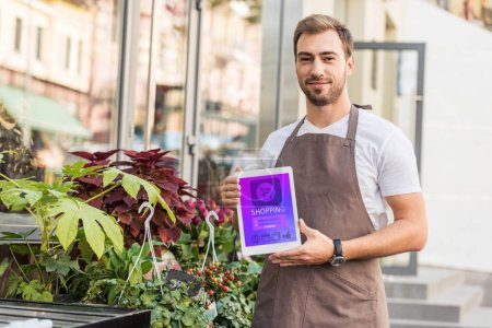 handsome florist holding tablet with shopping appliance near flower shop