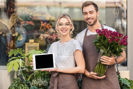 happy florists holding tablet with blank screen and burgundy roses near flower shop
