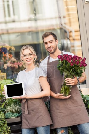 smiling florists holding tablet with blank screen and burgundy roses near flower shop