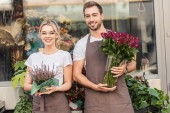 smiling florists standing near flower shop with potted plant and burgundy roses, looking at camera