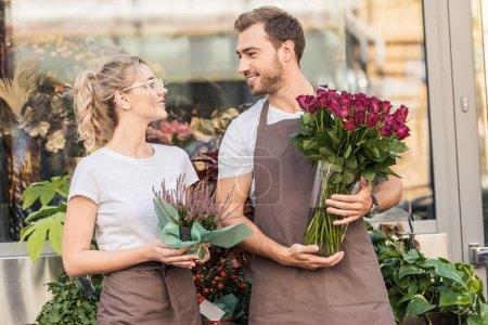 Foto de Floristas sonrientes, de pie junto a la tienda de la flor con planta en maceta y Borgoña rosas, mirando el uno al otro - Imagen libre de derechos