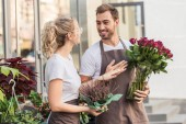 happy colleagues talking and standing near flower shop with potted plant and burgundy roses