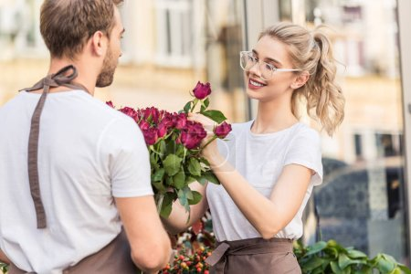 smiling florists selecting burgundy roses near flower shop