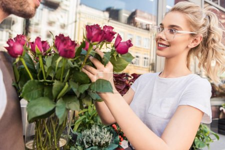 cropped image of smiling florists selecting burgundy roses near flower shop