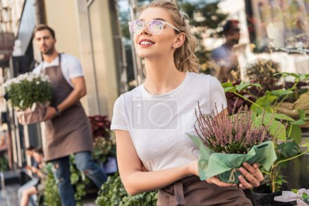 attractive florist holding potted salvia flowers near flower shop and looking up
