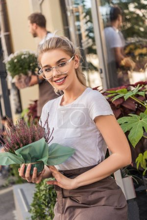 beautiful florist holding potted plant near flower shop and looking at camera
