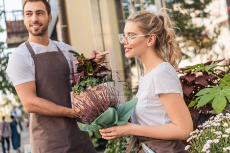Photo for Smiling florists holding potted plants near flower shop and looking away - Royalty Free Image