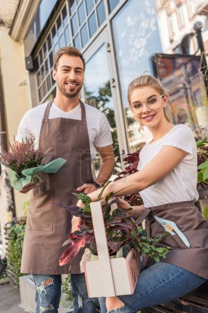 smiling colleagues holding potted plants near flower shop and looking at camera