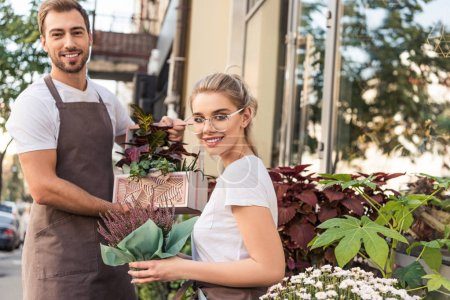 Photo for Smiling female and male florists holding potted plants near flower shop and looking at camera - Royalty Free Image