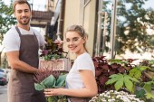 smiling female and male florists holding potted plants near flower shop and looking at camera