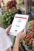 cropped image of florist using tablet with loaded instagram page near flower shop
