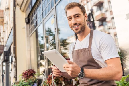 smiling handsome florist holding tablet near flower shop and looking at camera