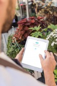 cropped image of florist using tablet with loaded skype page near flower shop