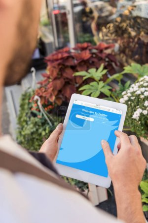 cropped image of florist using tablet with loaded twitter page near flower shop