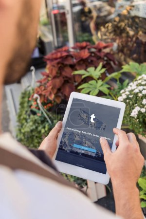 cropped image of florist using tablet with loaded tumblr page near flower shop