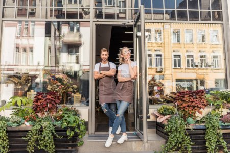 smiling female and male florists standing in open door of flower shop