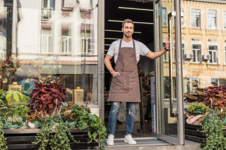 handsome florist in apron opening door of flower shop