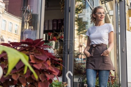 attractive florist in apron standing near flower shop and looking away