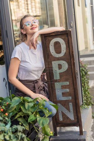 attractive smiling flower shop owner leaning on open sign