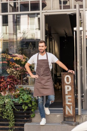 smiling handsome florist standing on stairs of flower shop and leaning on open sign