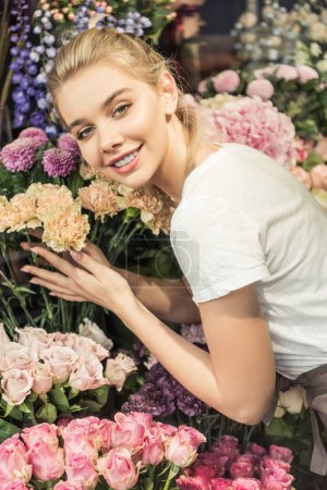 Photo for Smiling attractive florist hugging bouquets in flower shop and looking at camera - Royalty Free Image