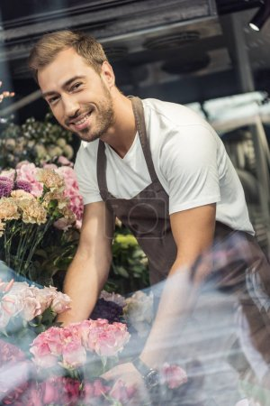 view through window of smiling handsome florist taking care of bouquets in flower shop and looking at camera