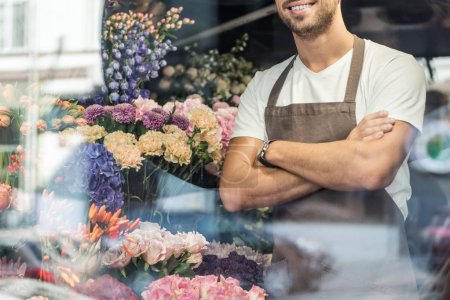 Photo for Cropped image of smiling florist standing with crossed arms in flower shop - Royalty Free Image