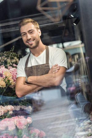 view through window of handsome florist in apron standing with crossed arms in flower shop and looking at camera
