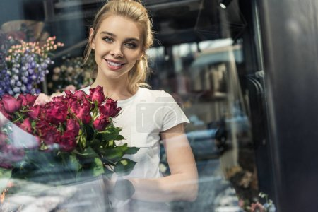 view through window of smiling attractive florist holding bouquet of burgundy roses in flower shop