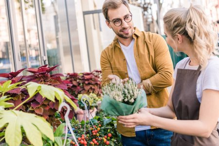 florist helping customer choosing potted plant at flower shop