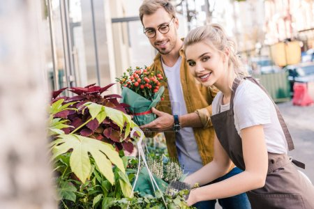 smiling florist and customer standing with plants near flower shop