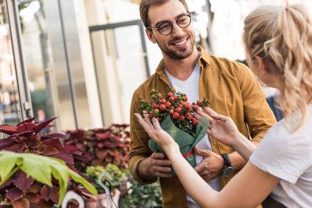 Photo pour Fleuriste qui décrit une plante en pot pour un client heureux près de fleuriste - image libre de droit