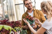 florist describing potted plant to happy customer near flower shop
