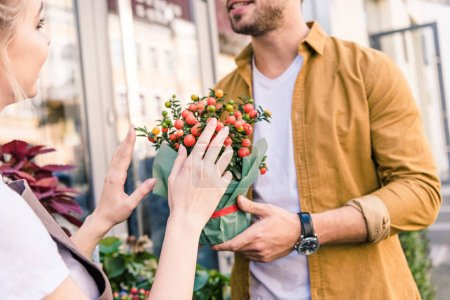 cropped image of florist describing potted plant with red berries to customer near flower shop