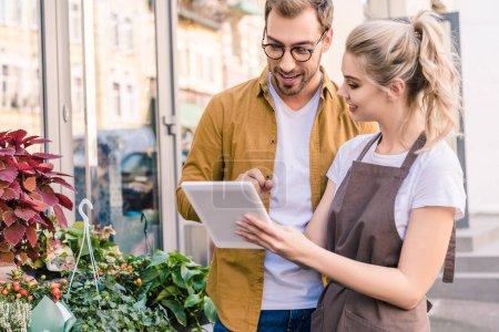 Photo pour Souriant, fleuriste et le client à l'aide de la tablette ensemble au magasin de fleurs - image libre de droit