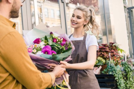 smiling florist giving beautiful bouquet of chrysanthemums to customer near flower shop