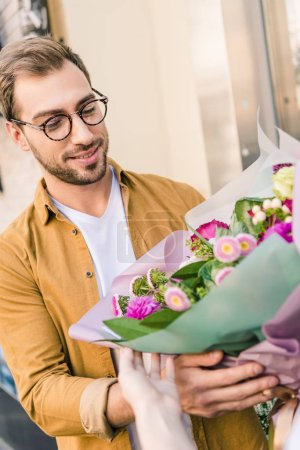 Photo for Florist giving beautiful bouquet of chrysanthemums to handsome customer near flower shop - Royalty Free Image