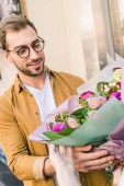 florist giving beautiful bouquet of chrysanthemums to handsome customer near flower shop