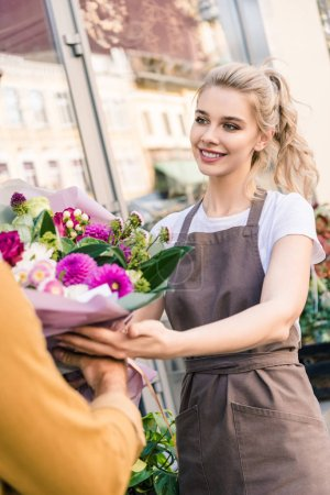 Photo for Smiling attractive florist giving beautiful bouquet of chrysanthemums to customer near flower shop - Royalty Free Image