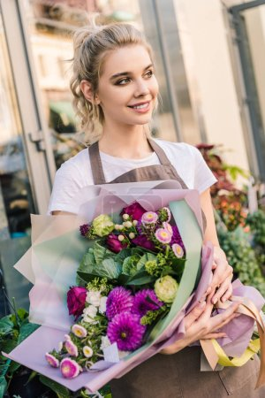 attractive florist holding beautiful bouquet of chrysanthemums near flower shop and looking away