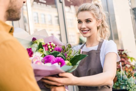 Photo for Smiling attractive florist giving bouquet to customer near flower shop - Royalty Free Image