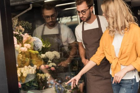 customer pointing on flowers to florist at showcase in flower shop