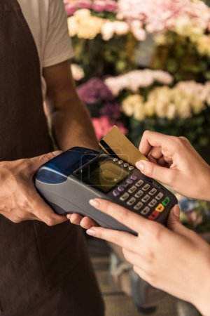cropped image of customer paying for flowers with credit card at store