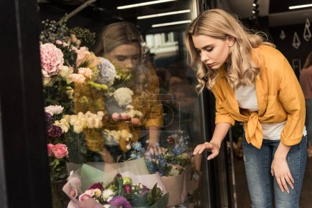 Photo for Attractive girl looking at showcase with flowers at store - Royalty Free Image