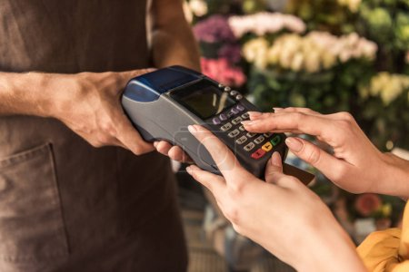 cropped image of customer paying with credit card at flower shop and entering pin code