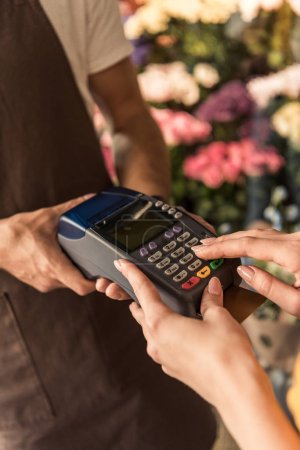 cropped image of customer paying with credit card at flower shop and entering pin code on payment terminal