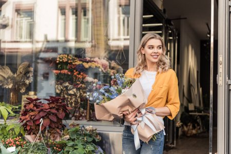 attractive smiling girl going out from flower shop with wrapped bouquet and looking away